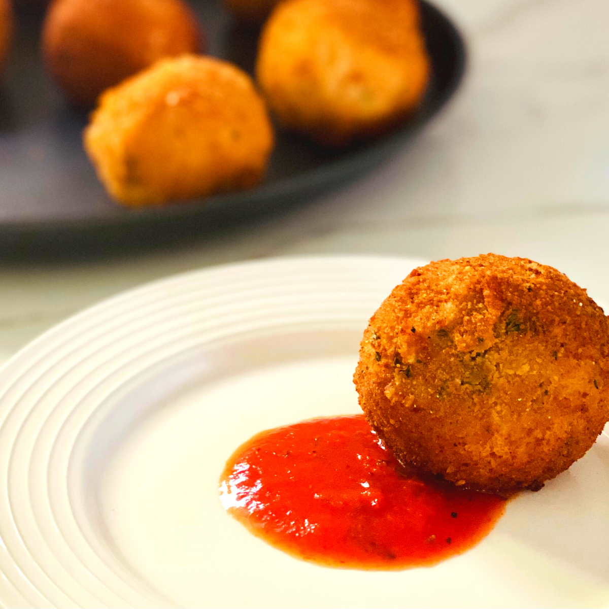 A fried arancini ball on a white plate with a dollop of red marinara sauce in the center.
