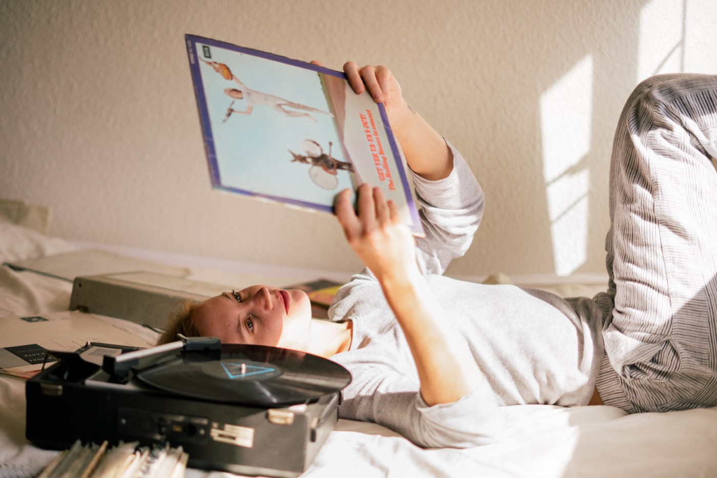 A woman reclines on a bed, listening to vinyls on a record player as she looks at the cover of an album.