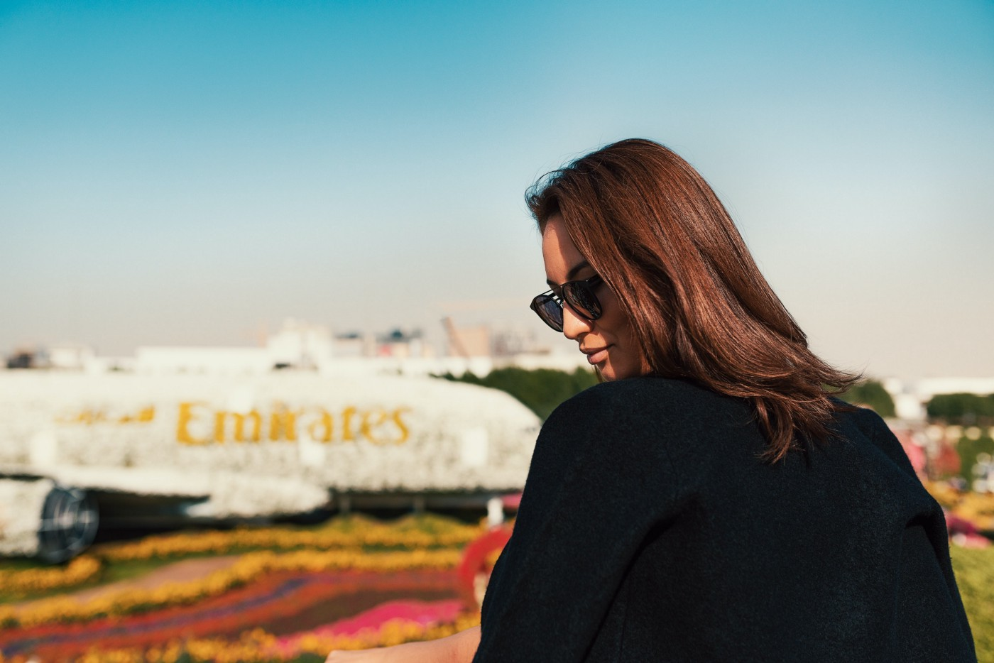 Woman in front of a floral version of the Emirates aircraft.