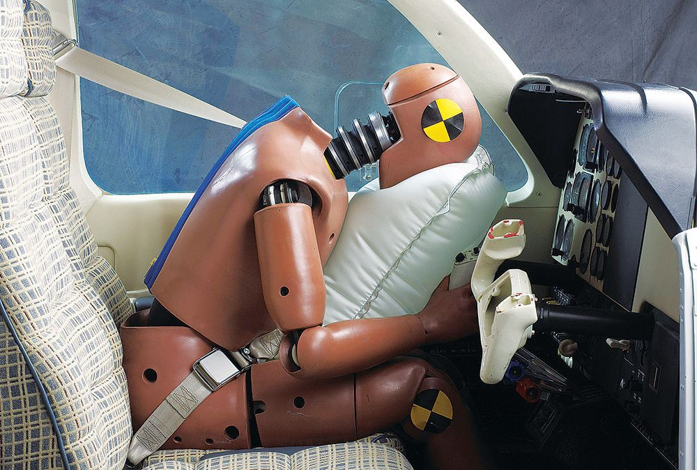 A crash dummy hitting a seatbelt airbag during a text in a small airplane.