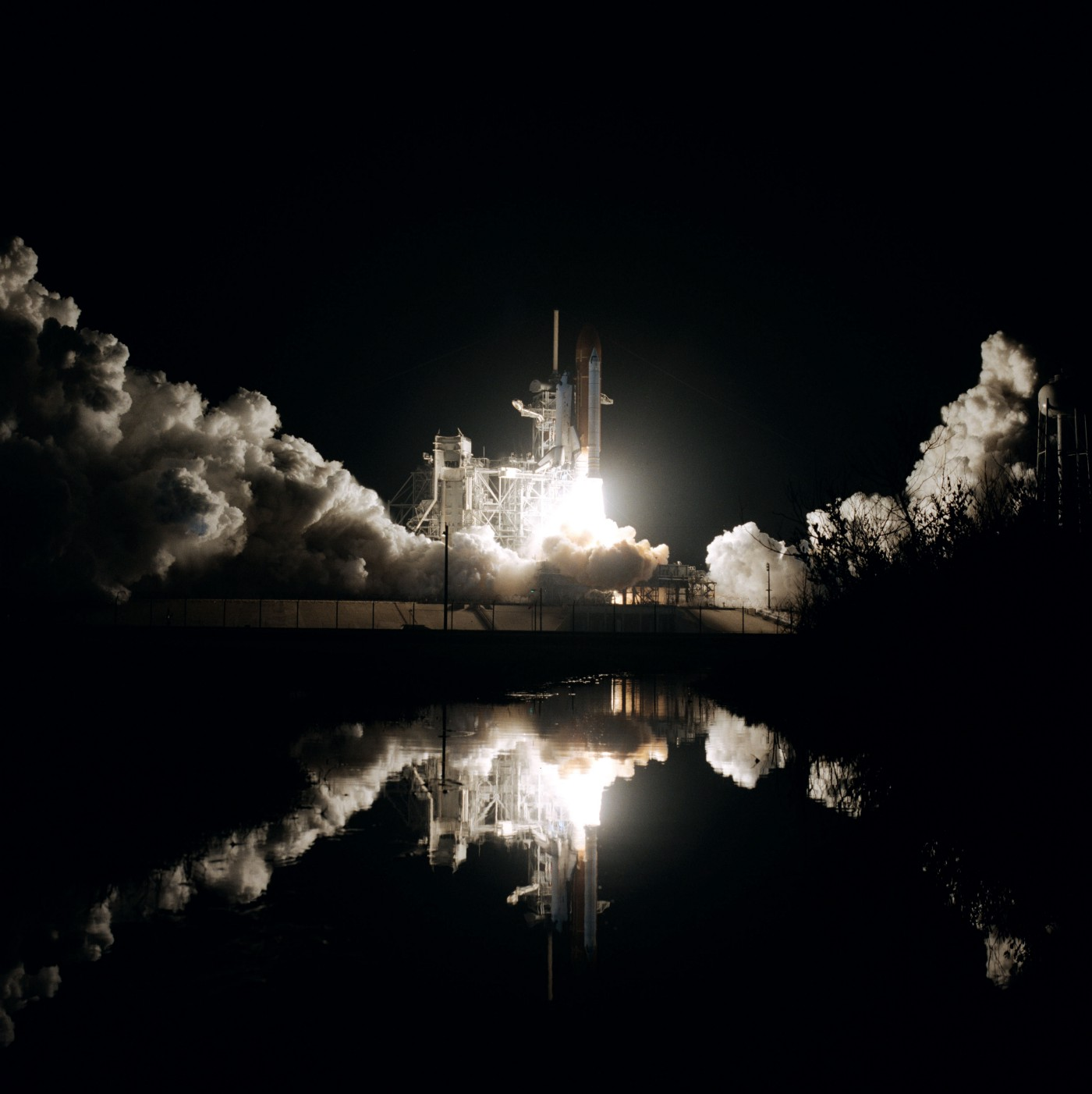 Nighttime Space Shuttle launch with fuel clouds and reflection