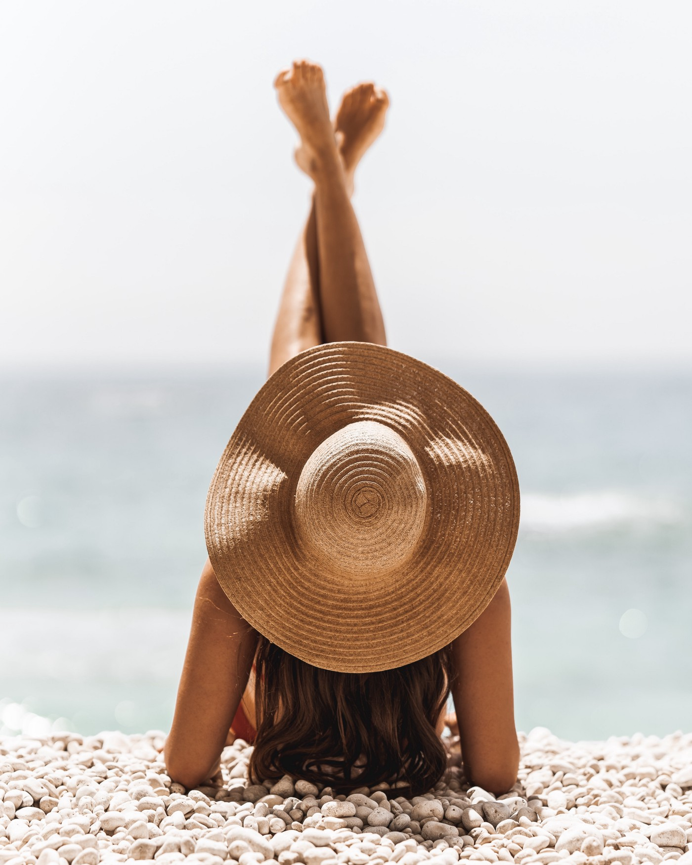 Woman sitting on a beach with a sun hat covering her face.