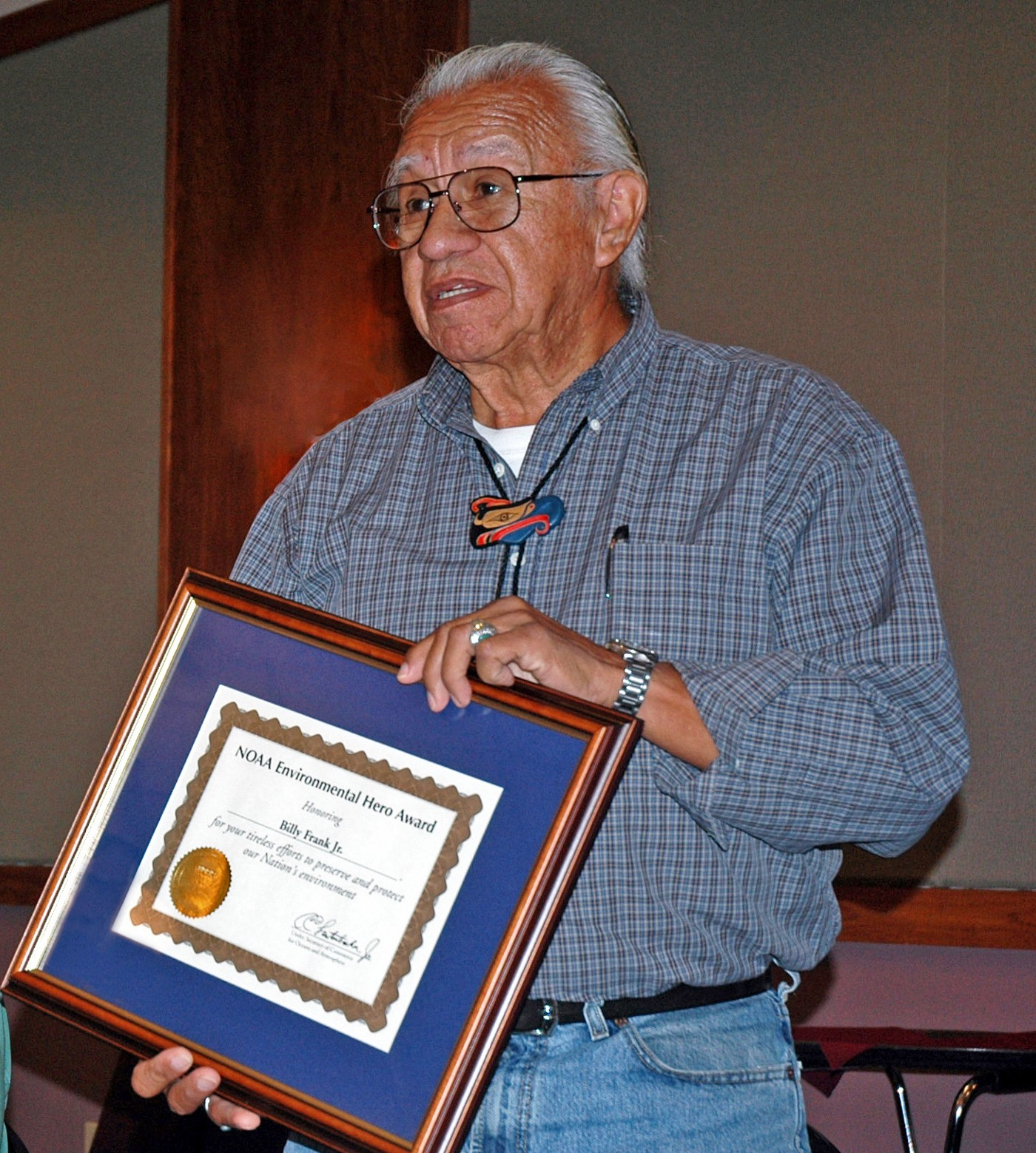 Photo of Billy Frank Jr. holding an award certificate from NOAA. Photo credit: Northwest Indian Fisheries Commission.