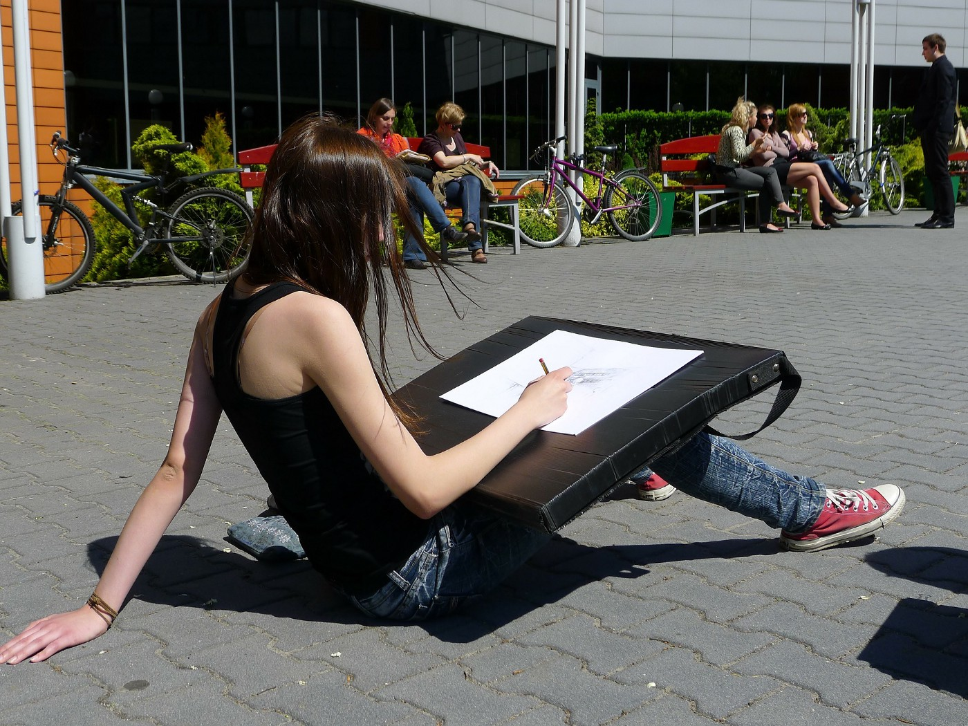 A young woman sketches outdoors, sitting on the ground. She is wearing a black tank top, jeans, and red sneakers