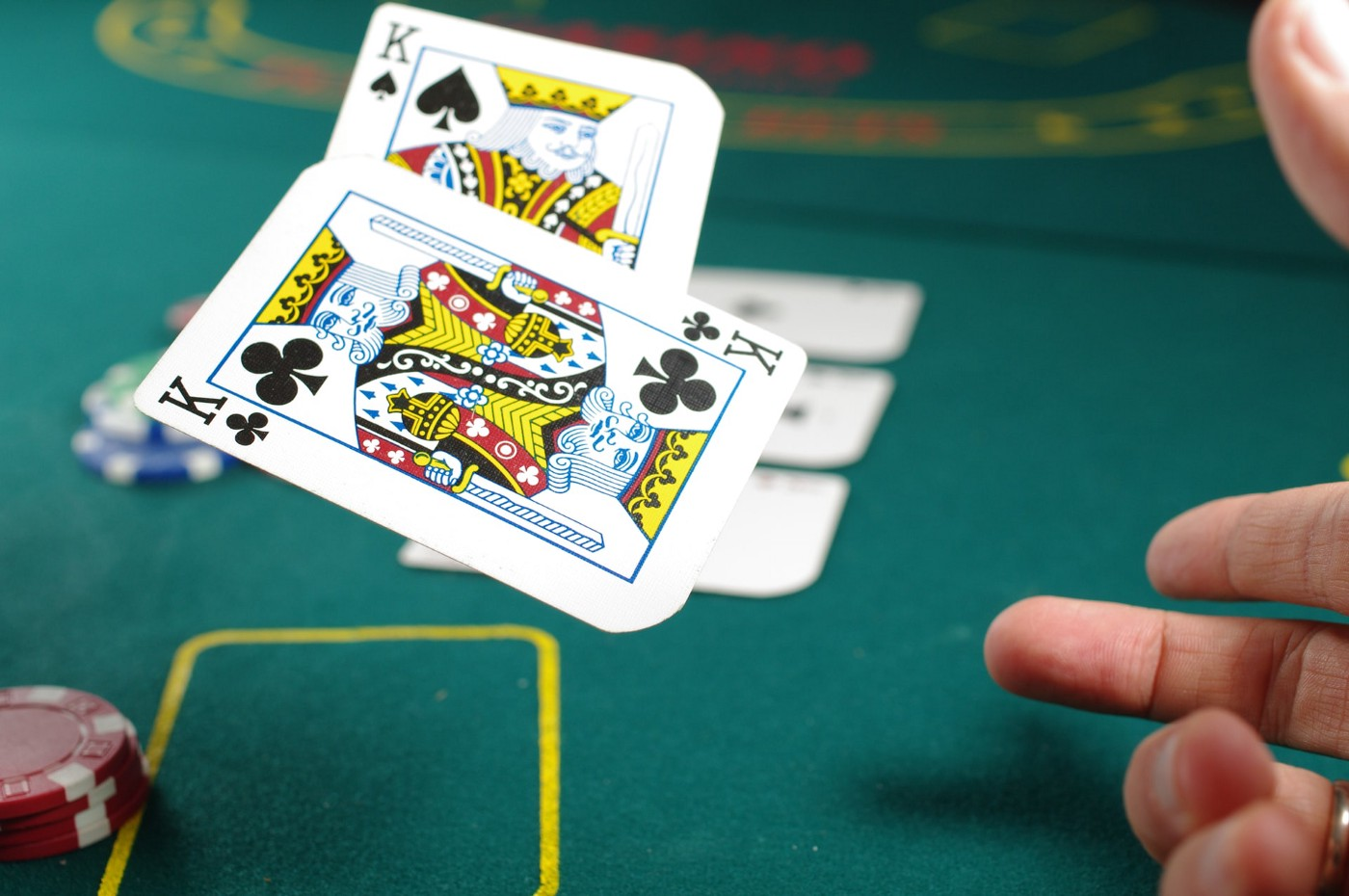 A hand throwing a pair of Kings cards on a poker table.