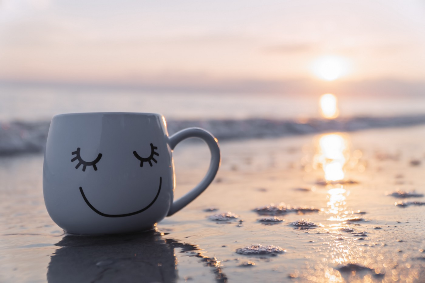 A smiley face mug placed on the sea shore.