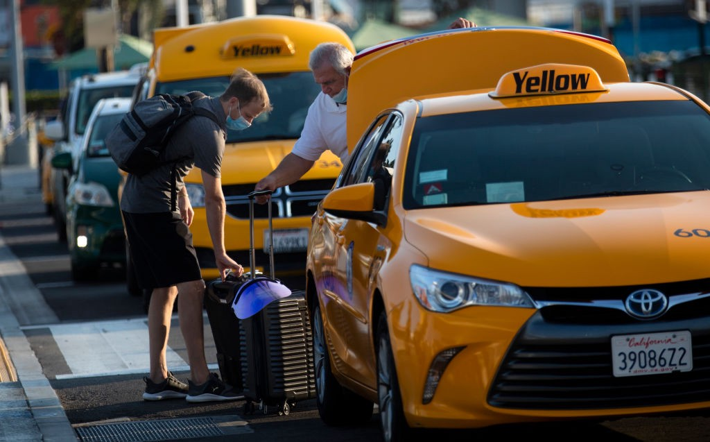 A cab driver helping a passenger load his luggage at LAX.