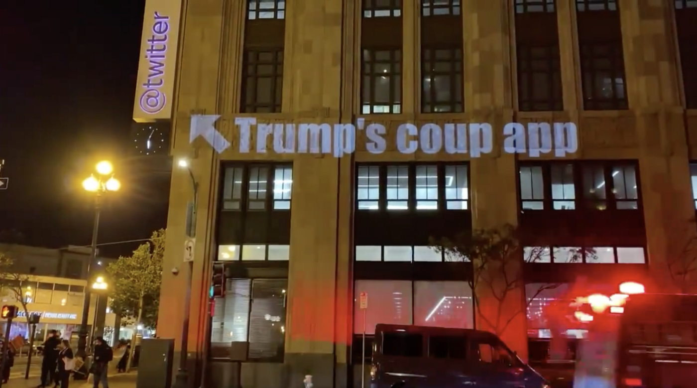 "Photo of ""Trump's coup app"" projected on Twitter headquarters with an arrow at the Twitter logo"