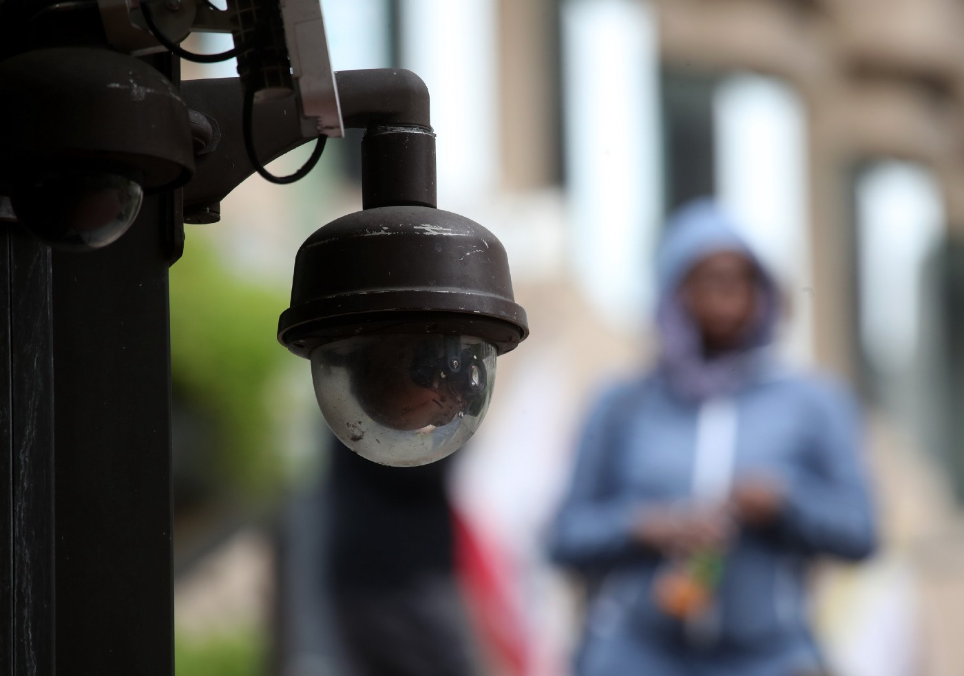 A video surveillance camera hangs from the side of a building in San Francisco, California.