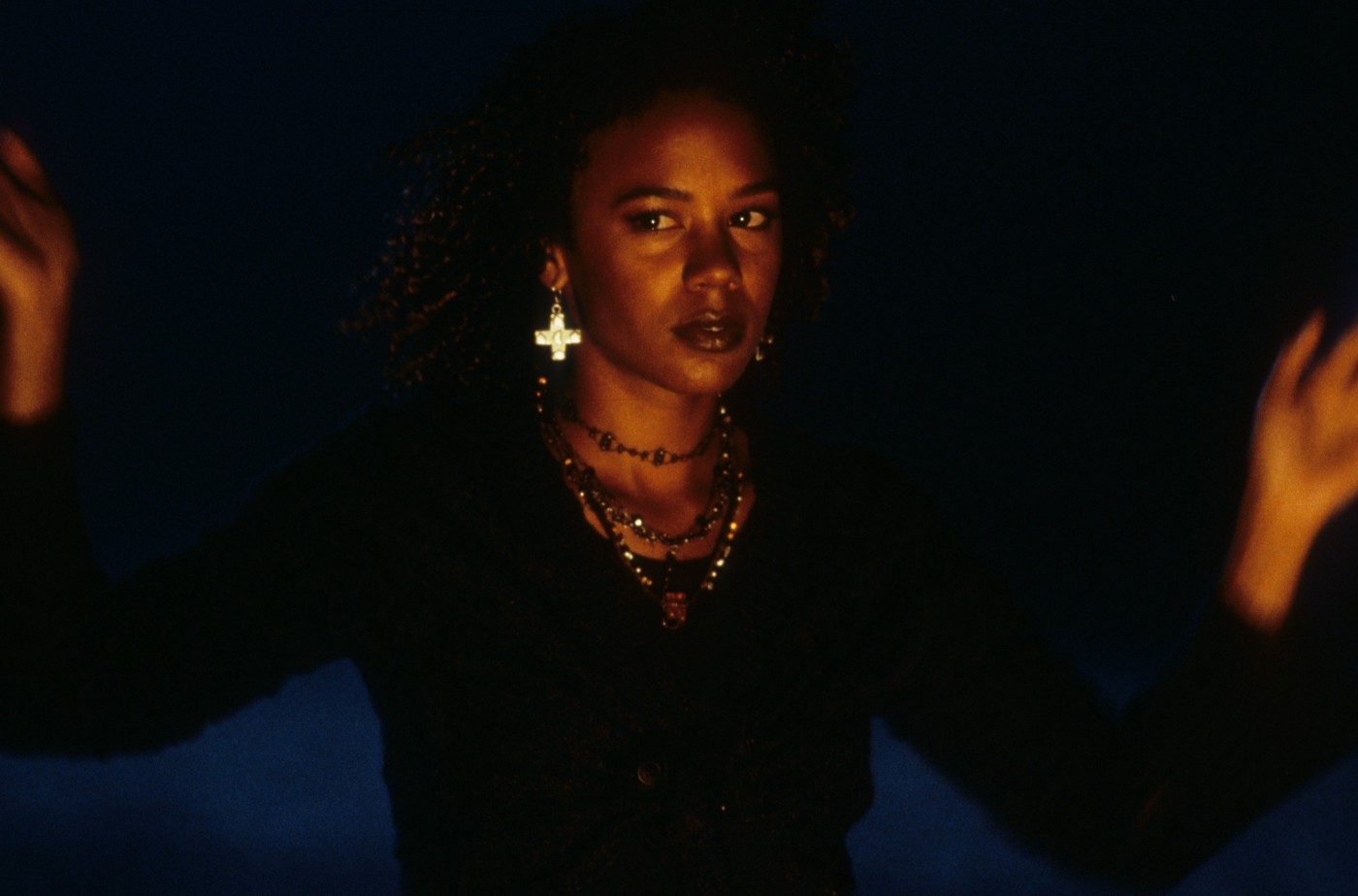 "Screenshot of Rachel True from ""The Craft."" She is wearing black and many necklaces."