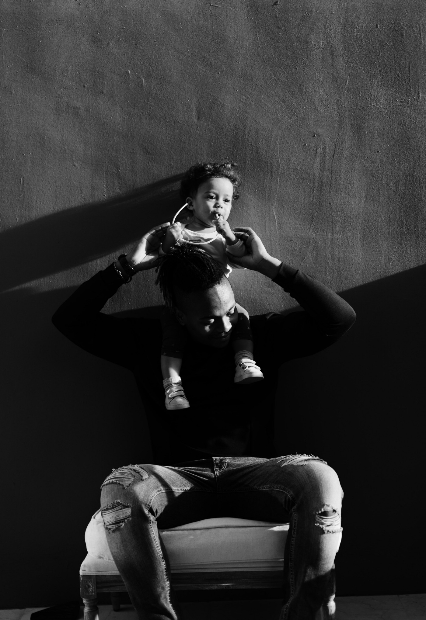 Black and white photo of a father holding young child.