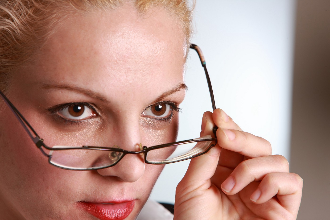 Close up of a woman's face. She is taking off glasses