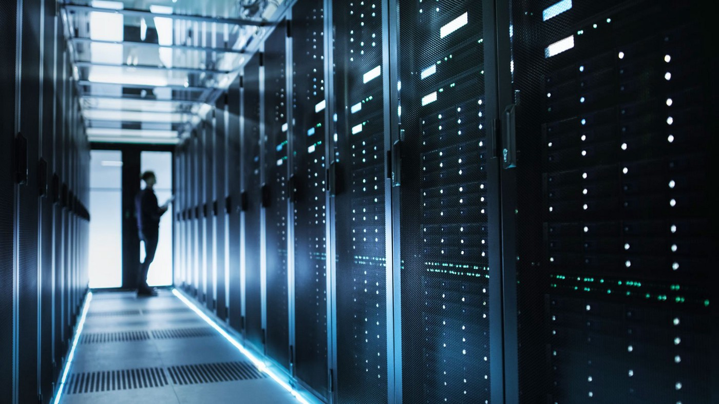 A dim room with server boxes. (https://www.streamdatacenters.com/the-top-4-advantages-of-a-private-data-center/)