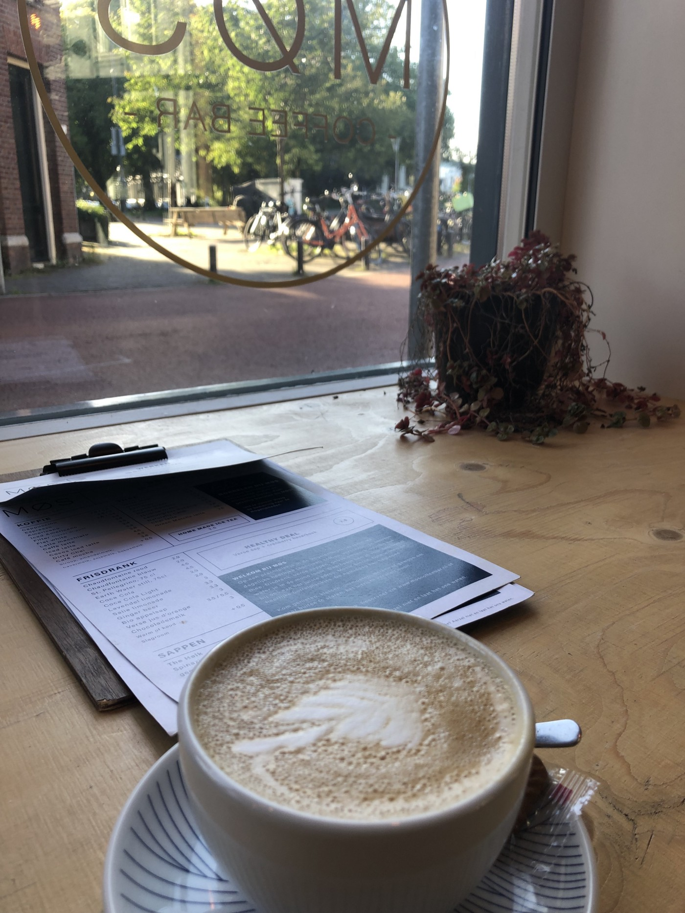 a view outside the cafe window with a coffee in the foreground