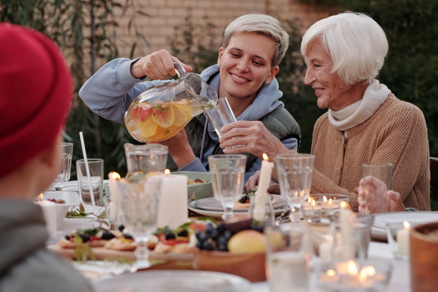 A younger woman is pouring lemonade to the older one — To Live the Hygge Lifestyle, Give Up on Toxic Individualism