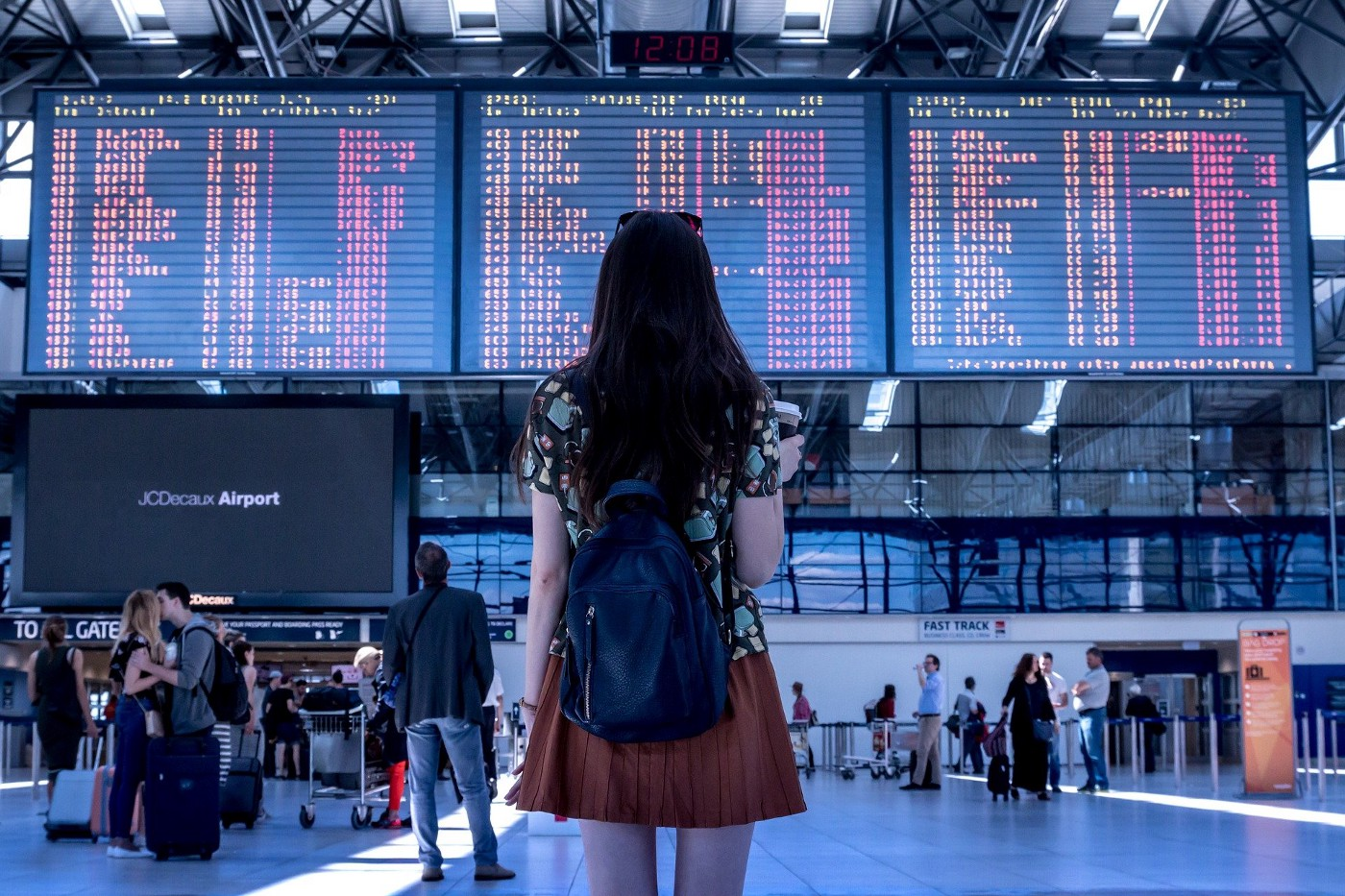 Girl looking at giant departure screen on airport.