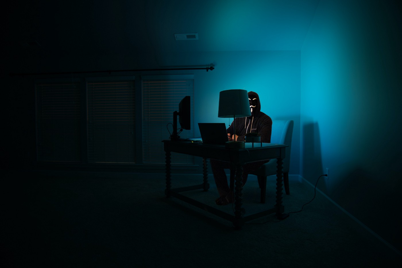 a man at a computer disguised as an anonymous hacker wearing a Guy Fawkes mask