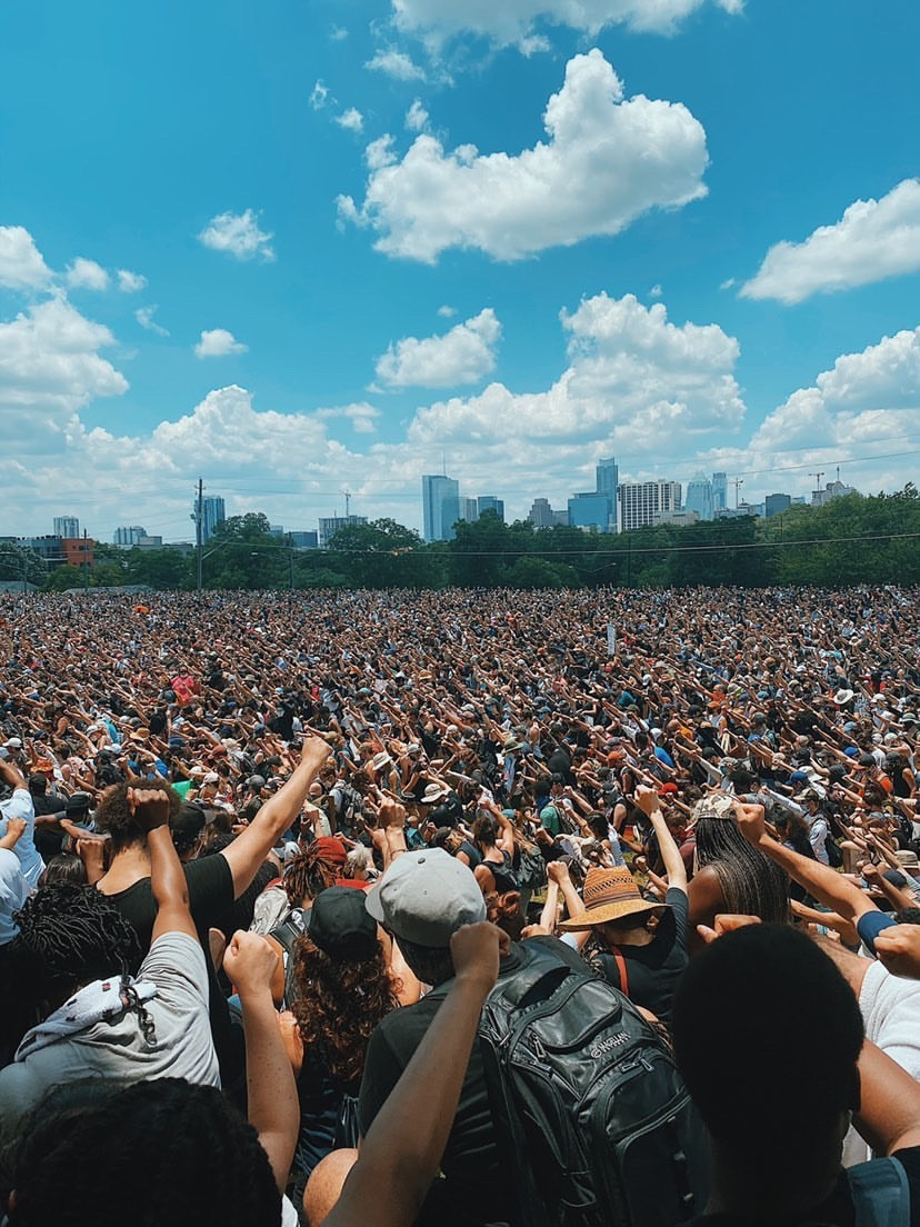 Thousands of people raise their fist at a rally at Huston-Tillotson University on a hot day in Austin, Texas.