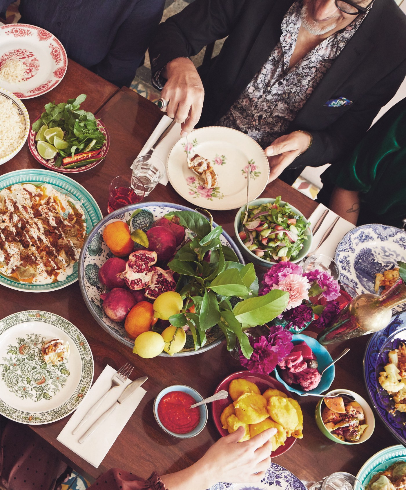 A family dinner with many dishes of colorful food.