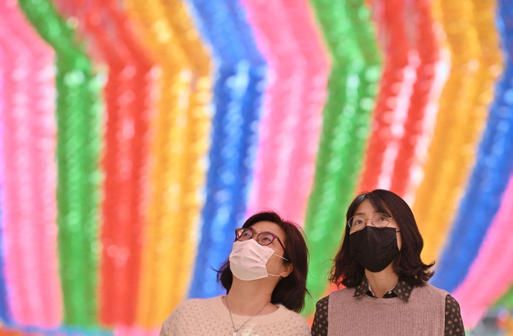 A photo of two Korean women wearing face masks at Jogyesa Temple in South Korea.