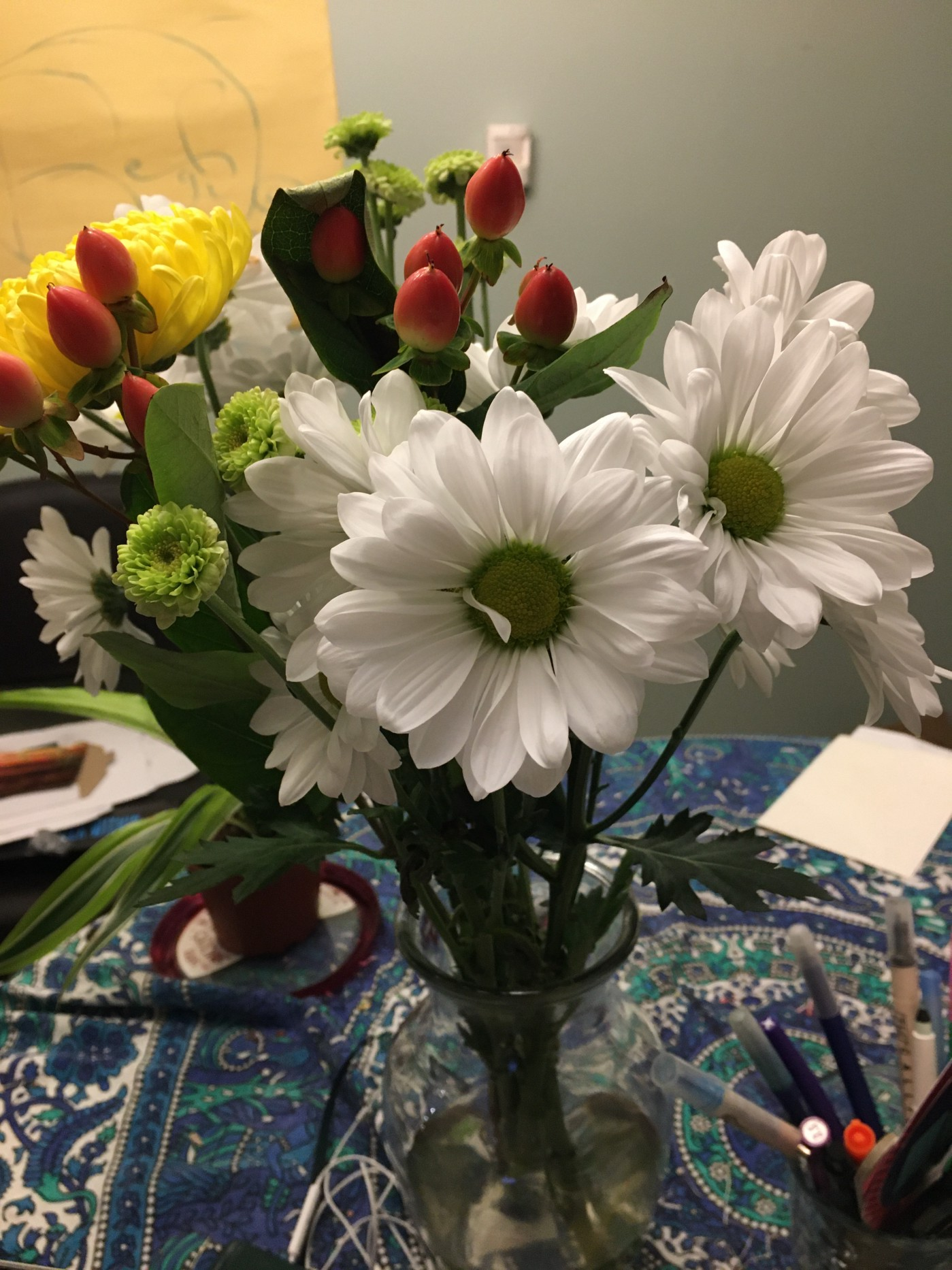 Bouquet with mostly whit chrysanthemums, a yellow one, and some types of red buds, in vase on Turquoise and blue Indian tablecloth with a few pens to the side.
