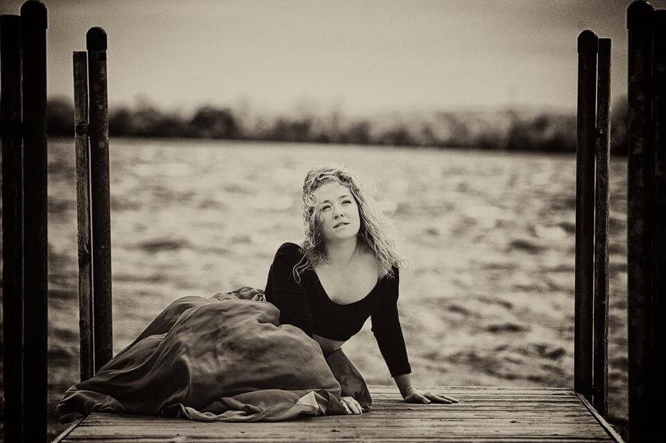 Black and white shot of a woman in a dress on a pier, water behind her.