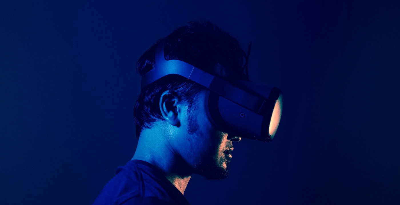 Stylish dark blue image of a man wearing Oculus headset.