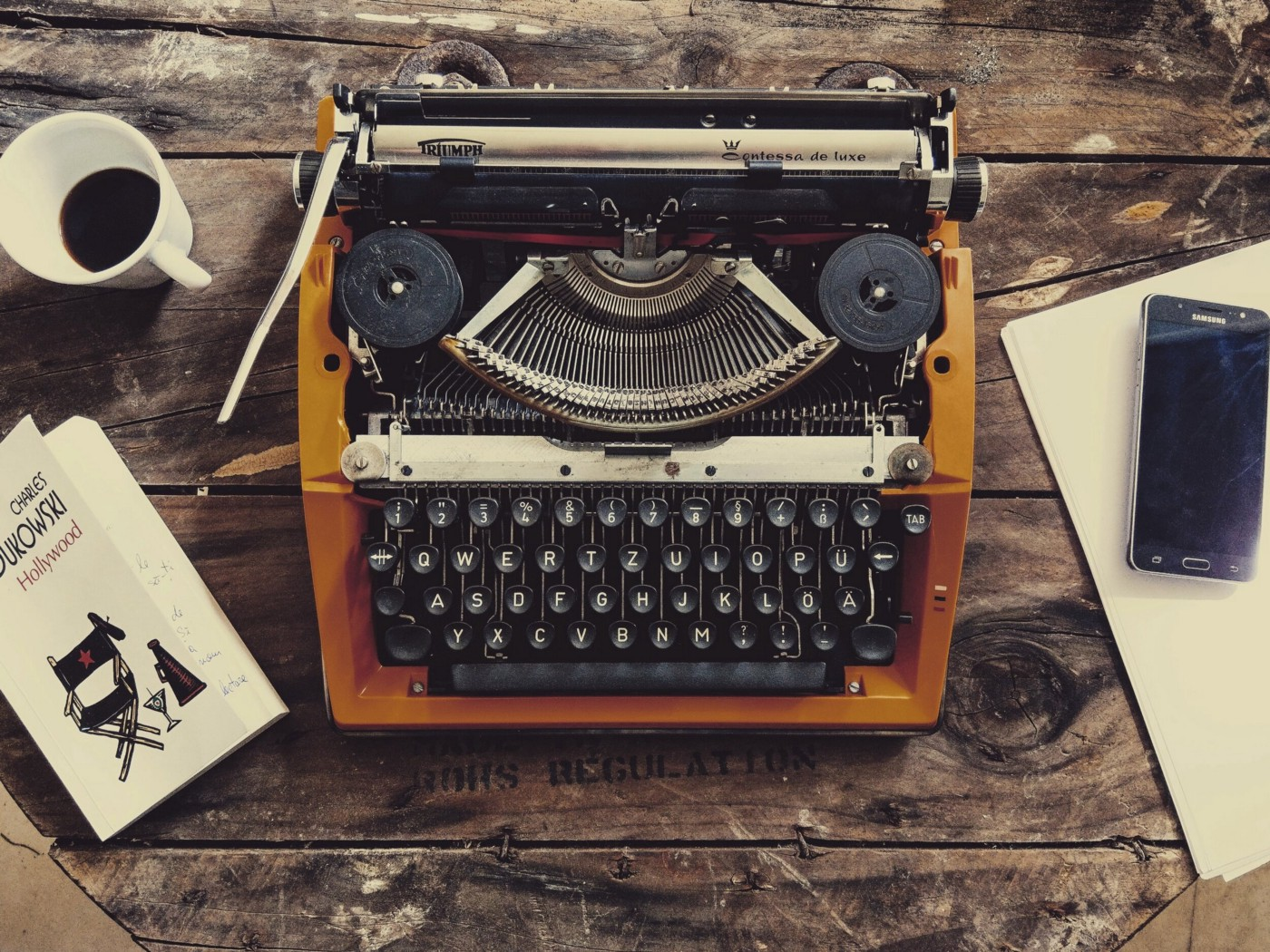 A yellow typewriter on a wooden table with a book, cup of coffee, notebook, and iPhone nearby.