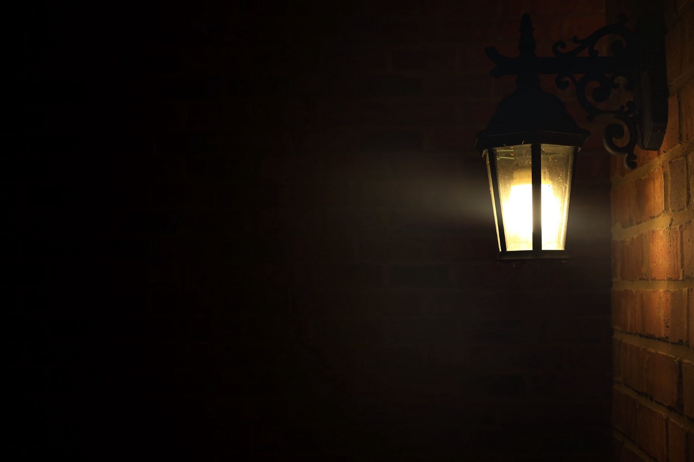 A lit porch light in a dark scene