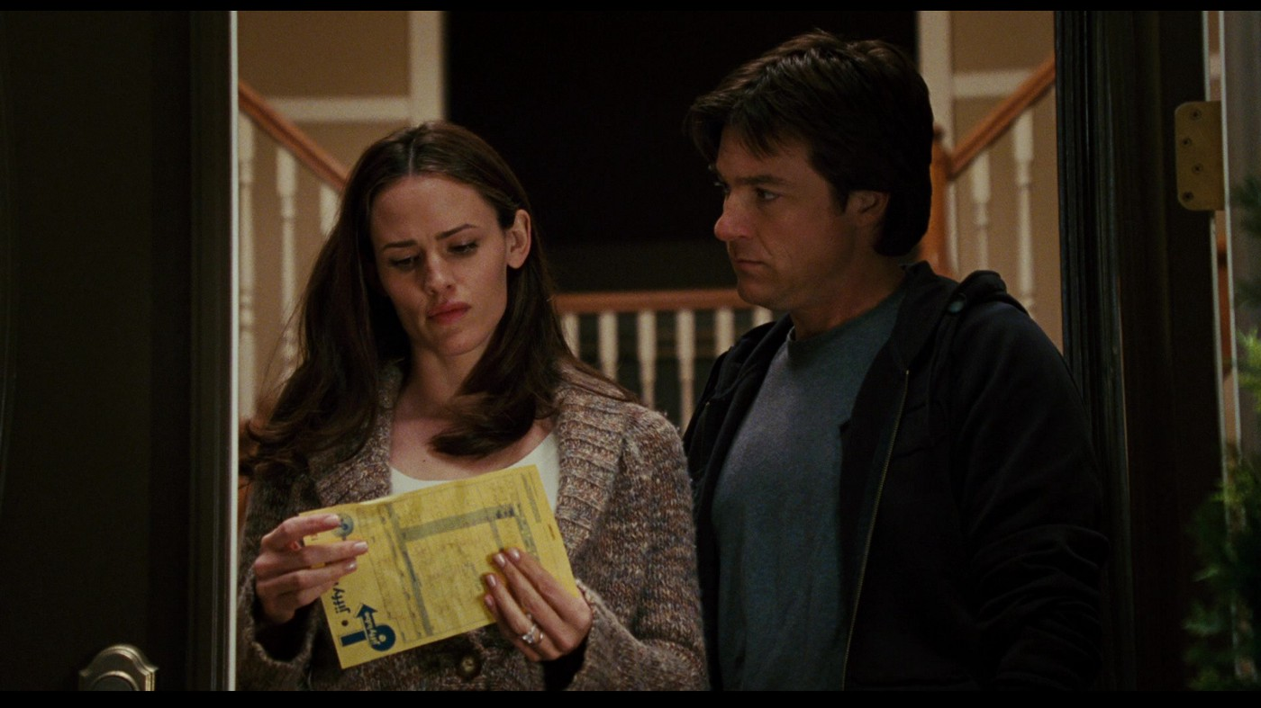 Jennifer Garner as Vanessa Loring holding a yellow paper in her hands as Jason Bateman as Mark Loring looks at her.