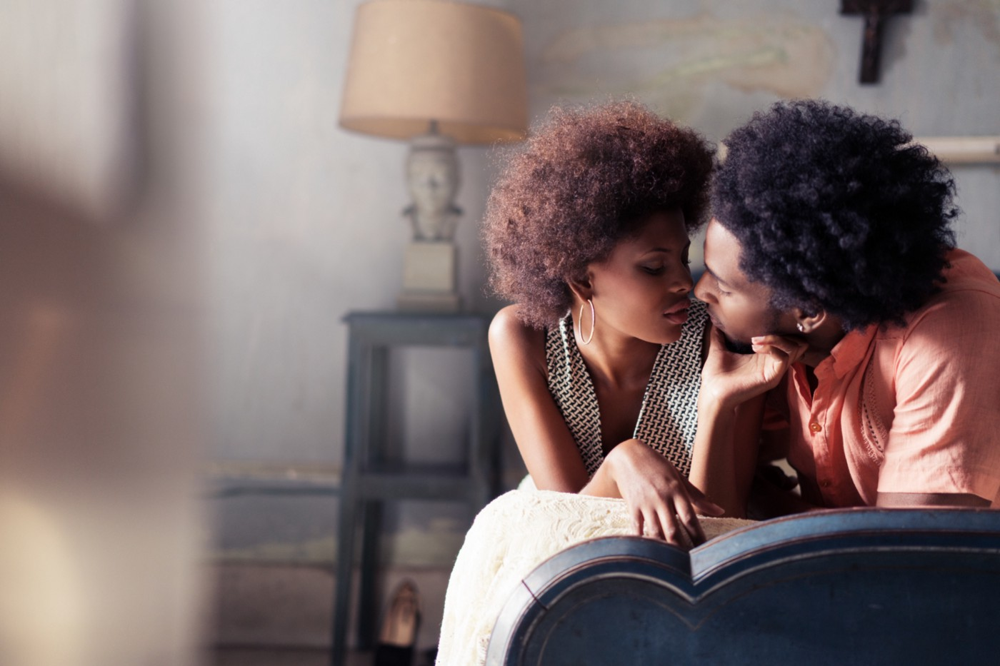 A photo of a black couple about to share a kiss on a bed.