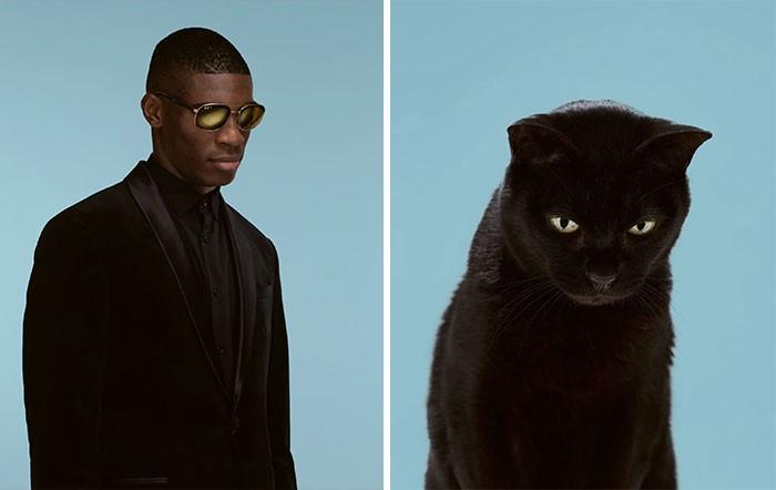 A black man wearing sunglasses looks ahead and towards the ground on the right, on the left a black cat does the same