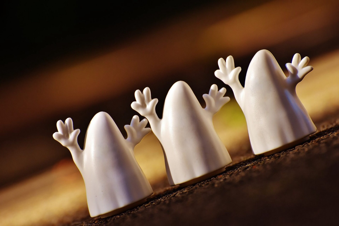 three toy ghosts with arms raised in a row