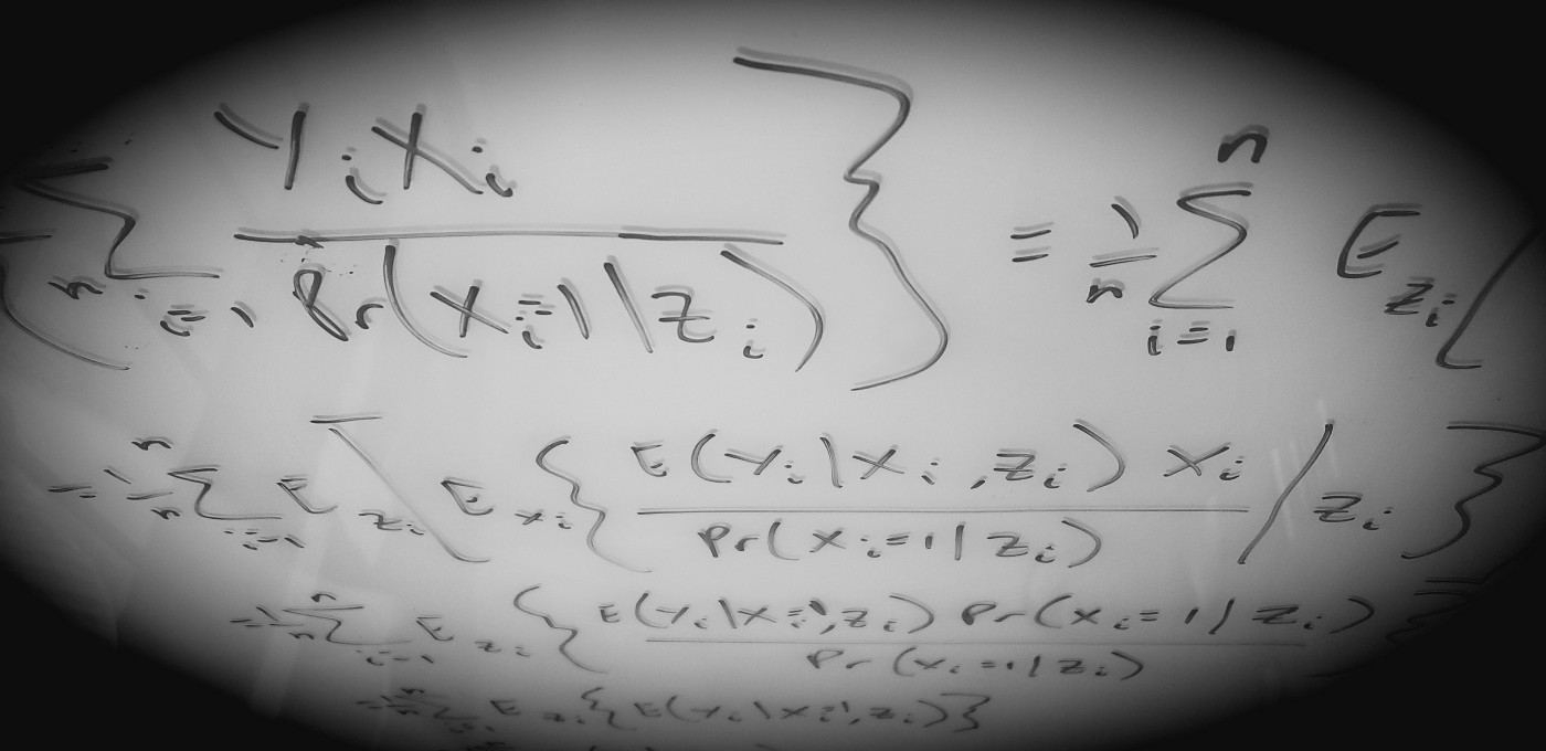 Photo of the author's glassboard filled with equations.