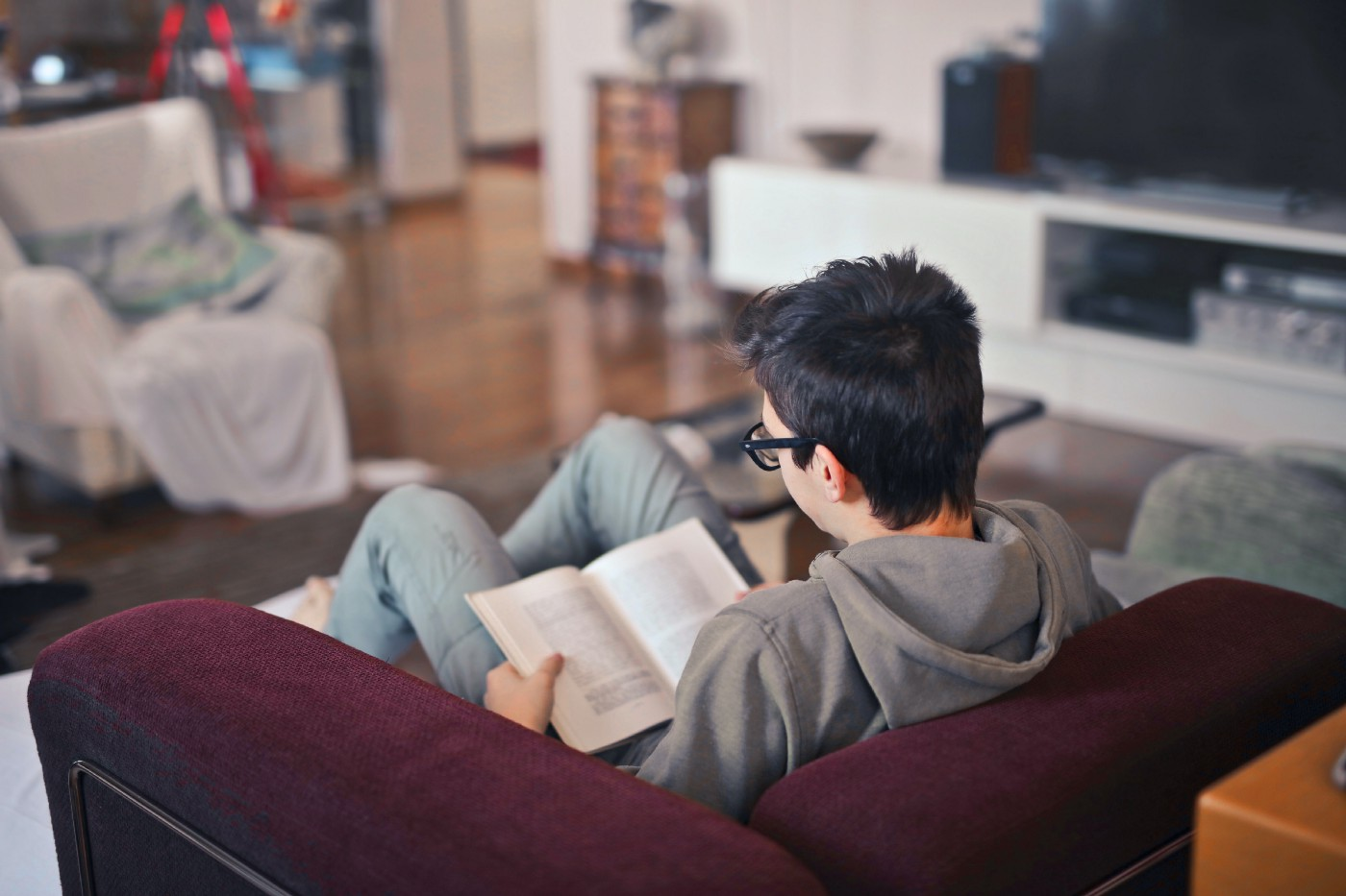 young lad reading on a sofa
