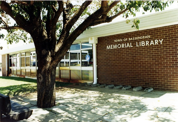 Street view of the Bassendean Memorial Library, with the name of the library on brickwork. A large tree is in the foreground