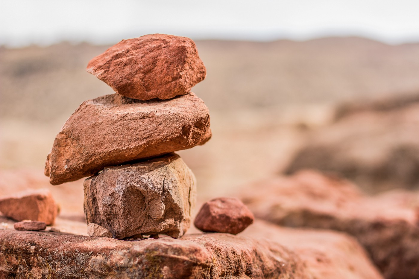 Three red rocks stacked on top of one another in a desert enviroment.