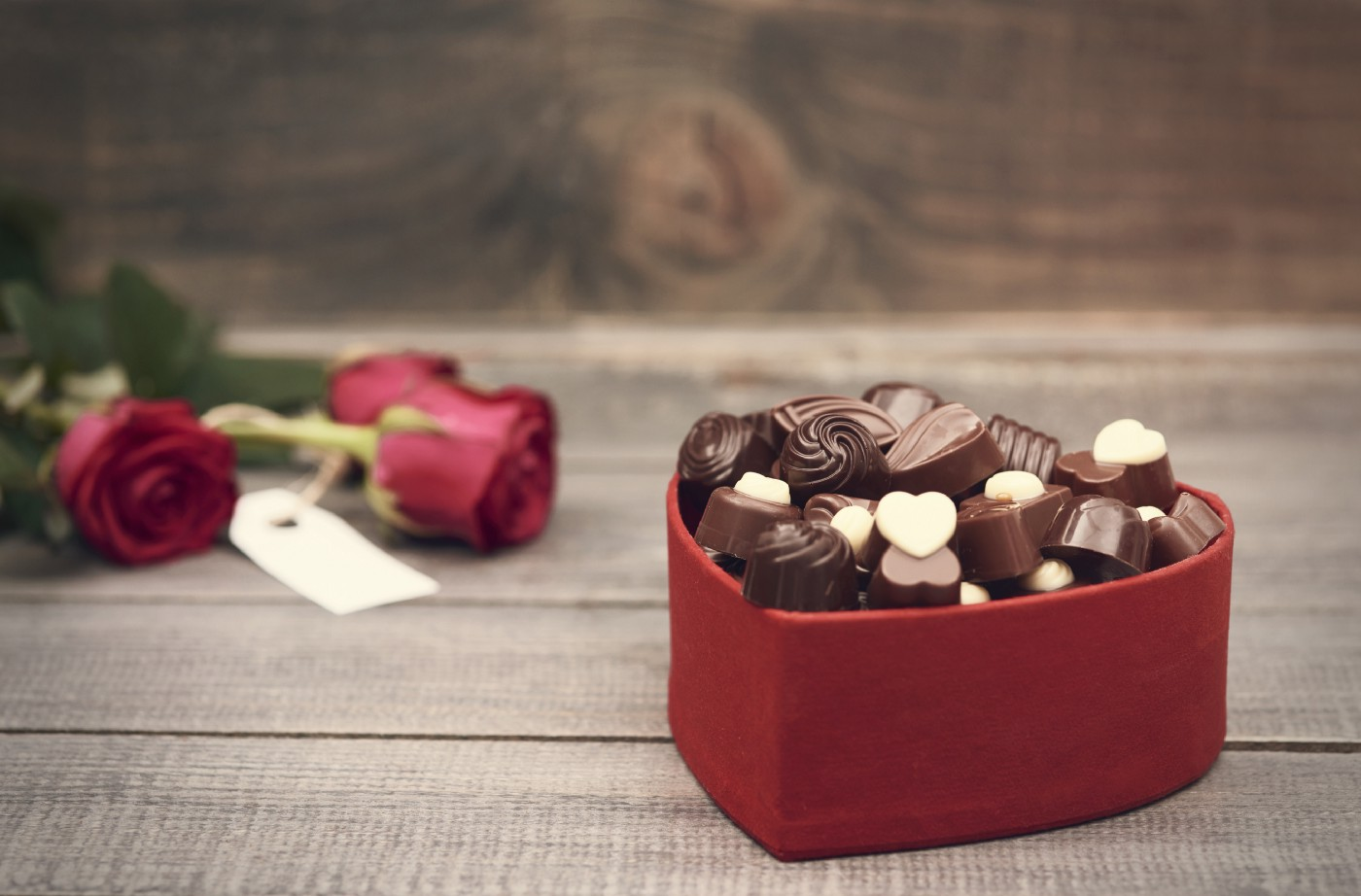 A box of chocolates next to roses.