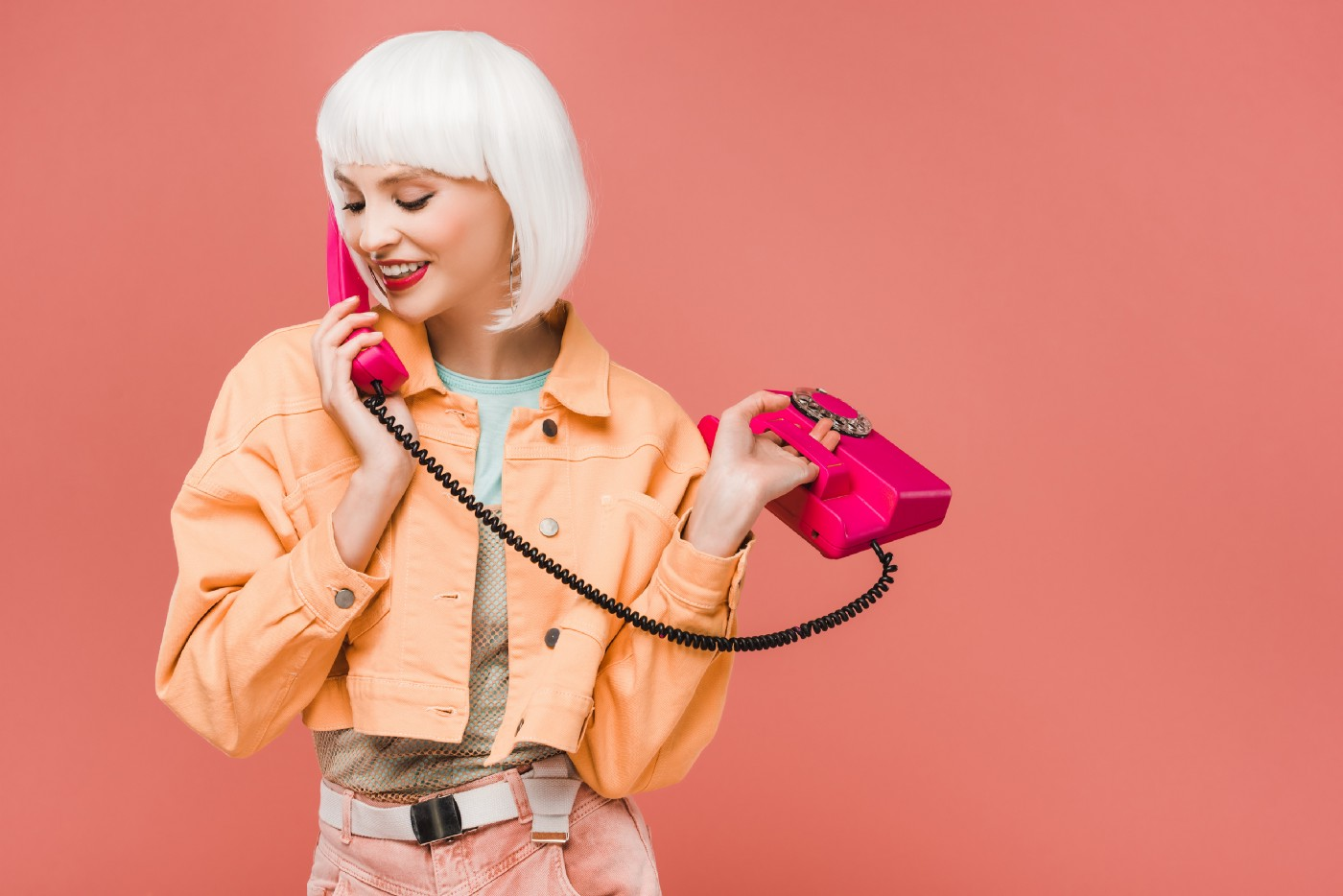 young woman in white-blonde wig wearing an orange jacket talking on a hot pink corded phone on dusty rose background