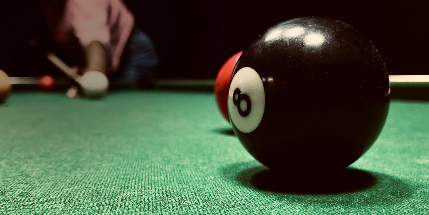 girl shoots cue ball toward 8 ball in the forefront
