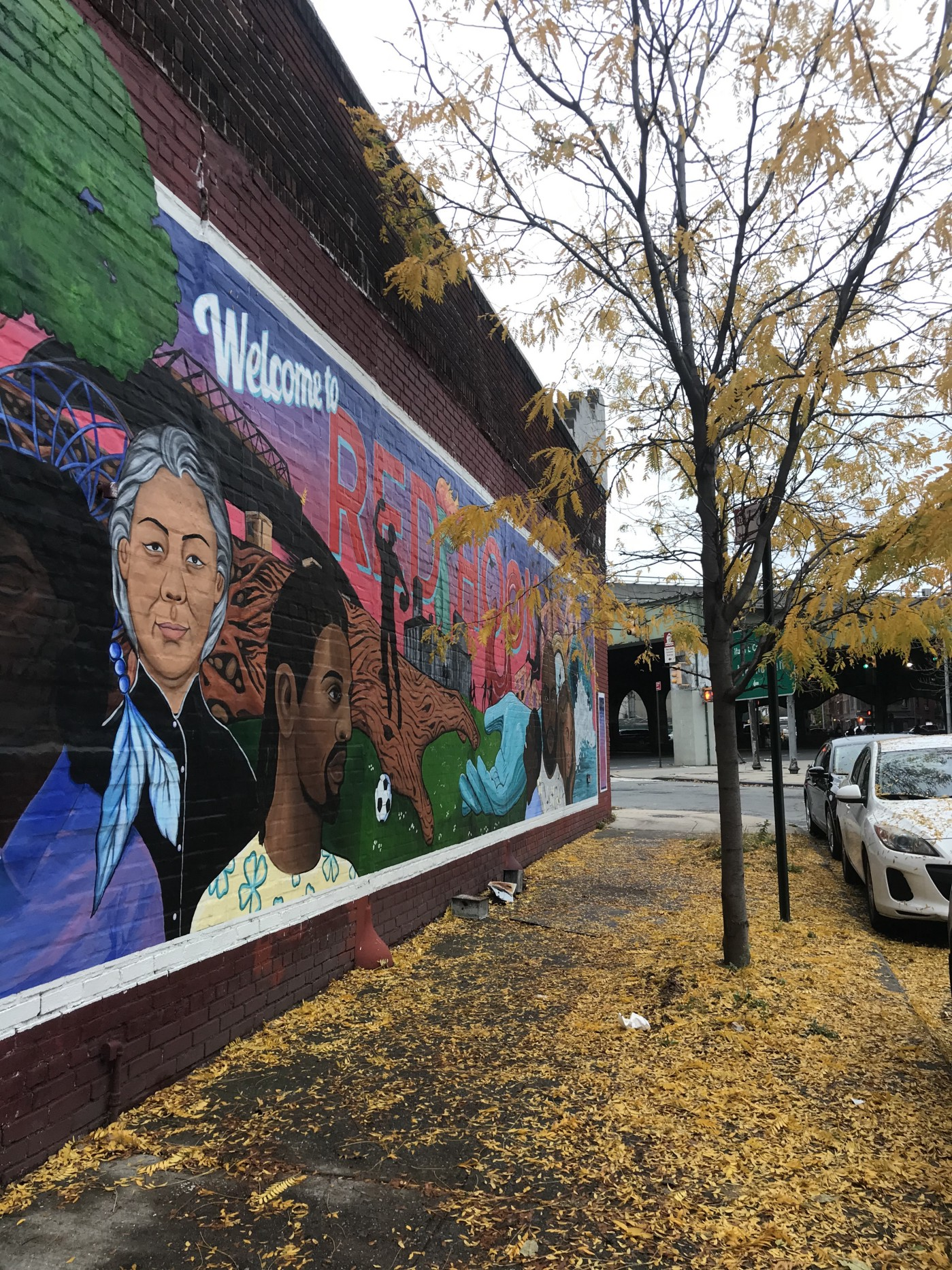 Colorful wall art depicting diverse people lives on a Red Hook building next to black tree with falling yellow leaves