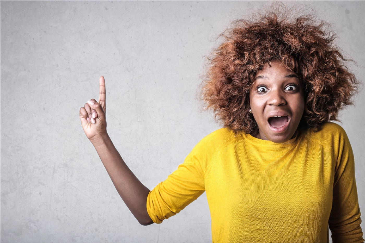 Picture of a woman appearing to be thrilled and holding up one finger, indicating the headline. Make money online—the best side hustles for 2021.