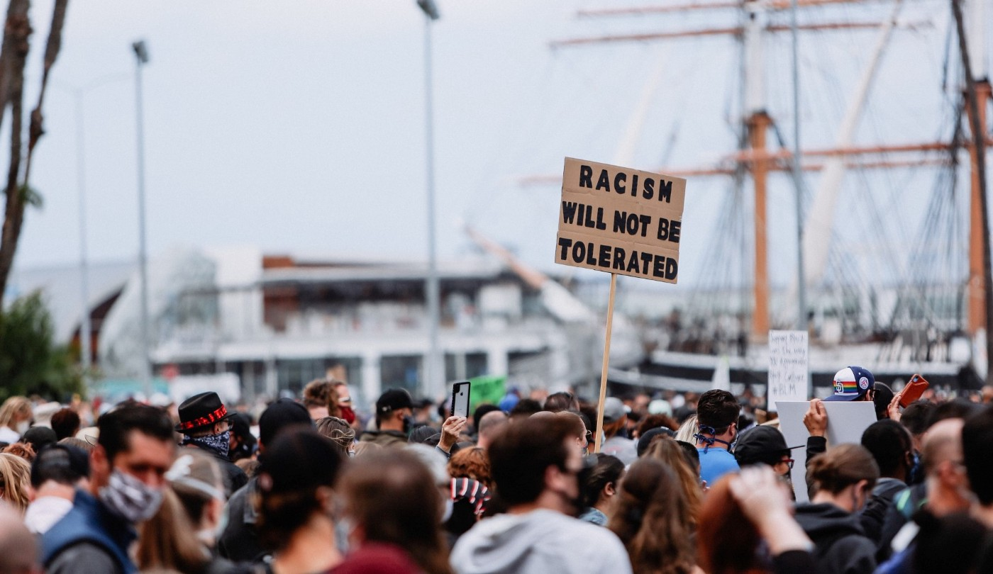 """A crowd protesting with a sign held up saying """"Racism will not be tolerated""""."""