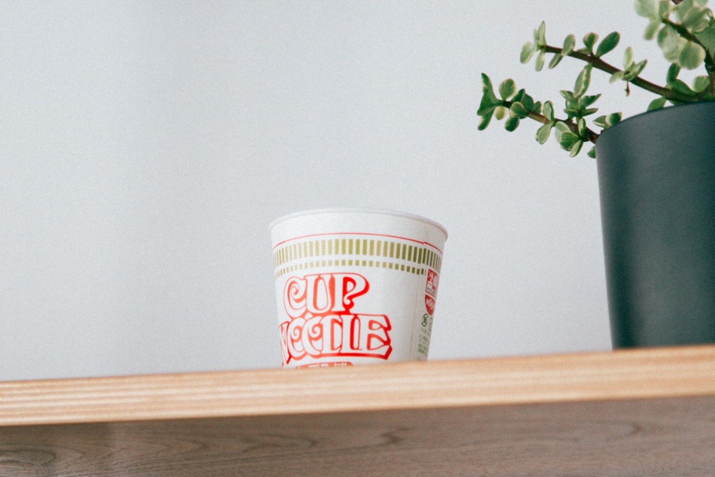 A Cup Noodle brand cup of ramen sitting on a wooden shelf next to a potted plant.