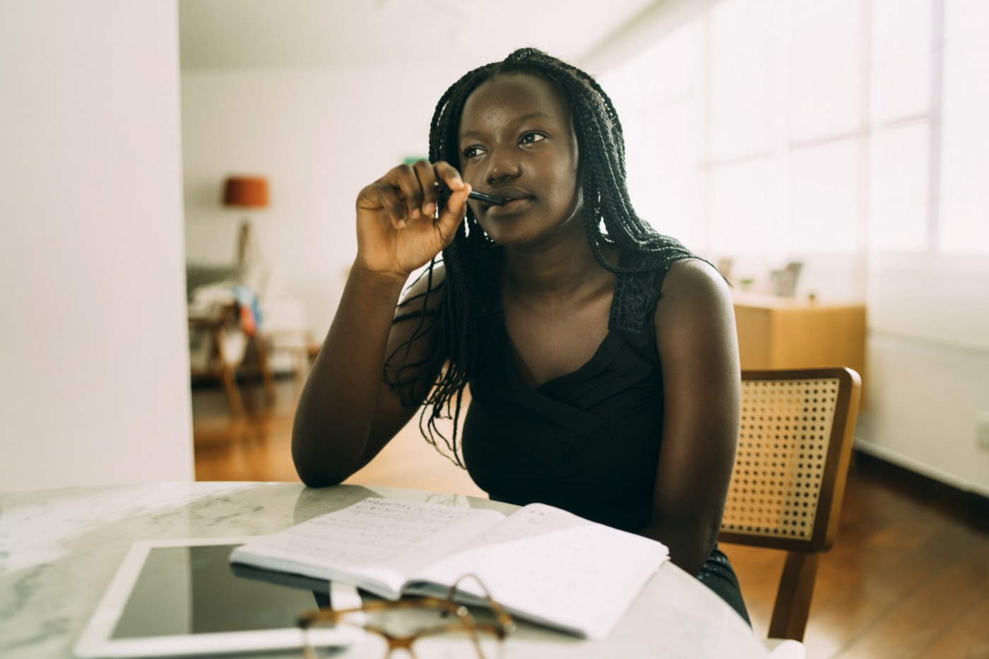 Black woman mulling her thoughts as she writes in her journal while sitting at a table.