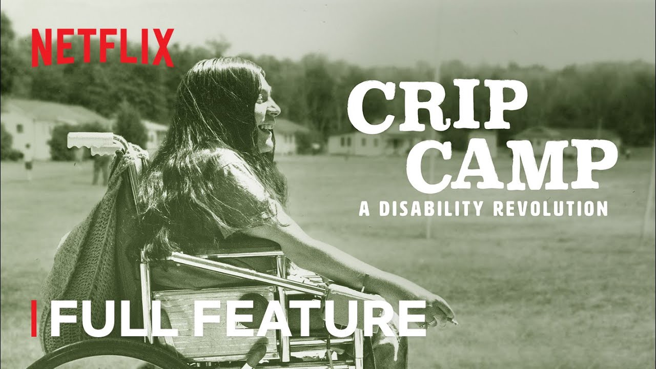 Promotional photo for Netflix's Crip Camp — a person in a wheelchair with long hair, smiling