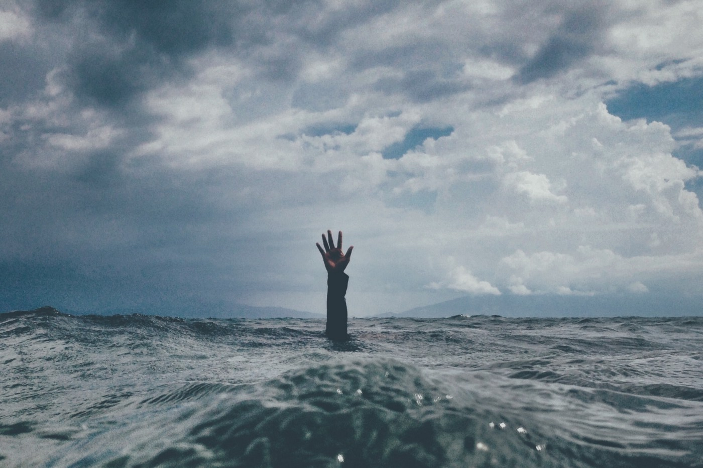 human hand rising from the ocean