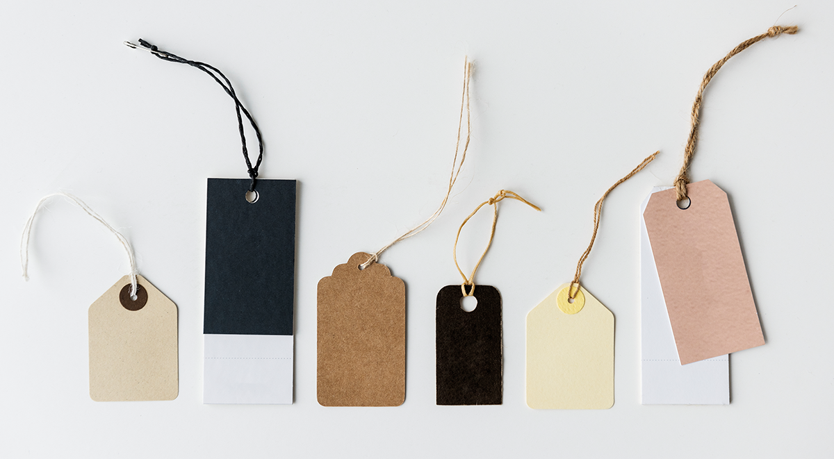 Clothing tags of different sizes and colours are exposed on a white surface