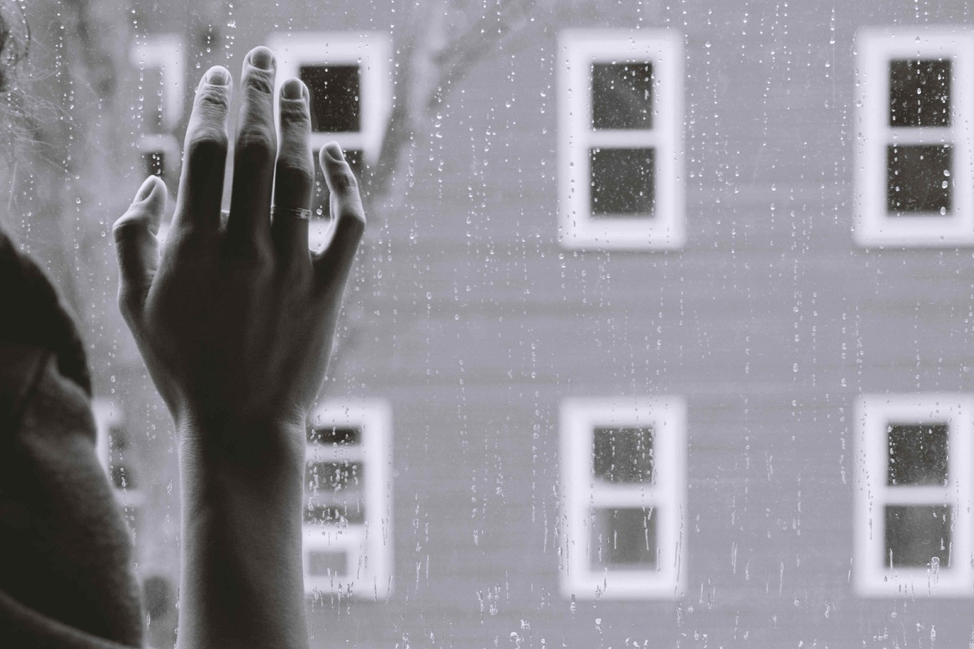 Hand on window, looking out over a rainy day, grayscale