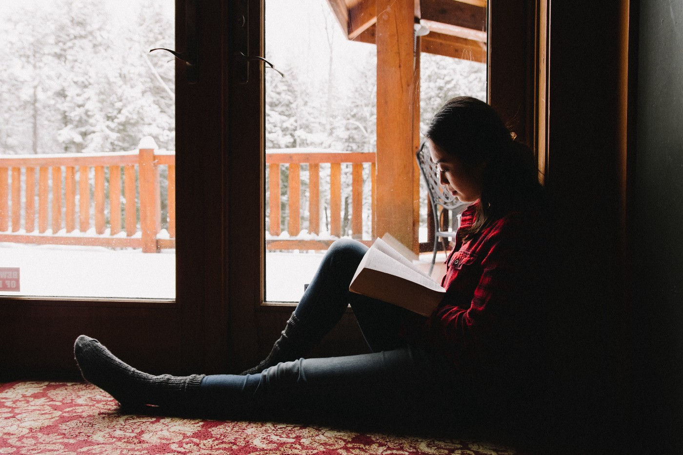 A woman reads a book on the carpet of her home with the natural light of a winter wonderland in her backyard illuminating the background.
